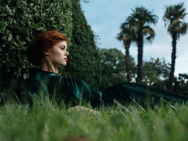 Женщина в зеленом платье лежит на траве природы и роскошной модели животного