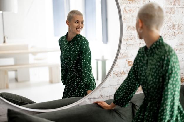 緑のドレスを着た女性が自宅の鏡で自分自身を見ています