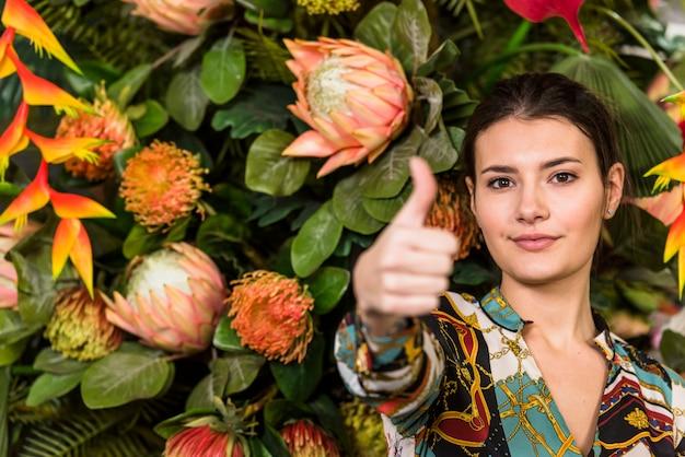 Женщина в зеленом доме, показывая большой палец вверх