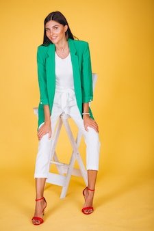 Woman in green jacket sitting on chair on yellow background