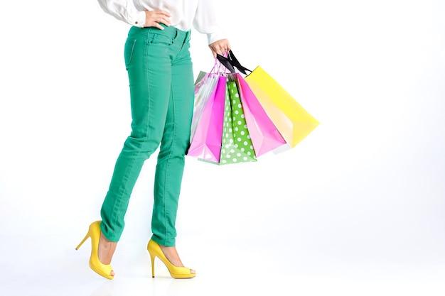 흰색 바탕에 쇼핑백과 녹색 바지에 여자