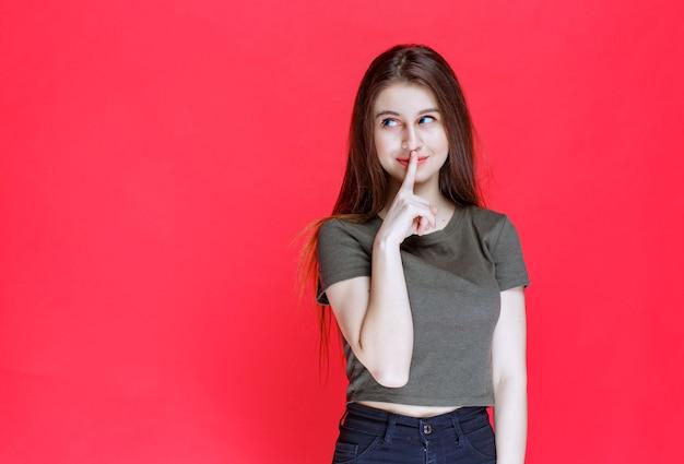 沈黙を求める緑のシャツを着た女性。