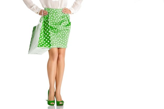 白い背景で隔離の買い物袋と緑のスカートの女性
