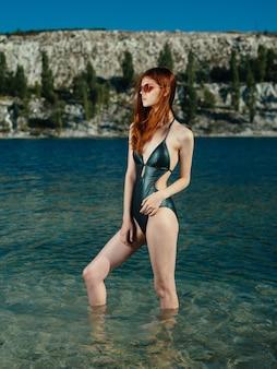 緑の水着の女性が透明な水の川のサングラスモデルに立っています
