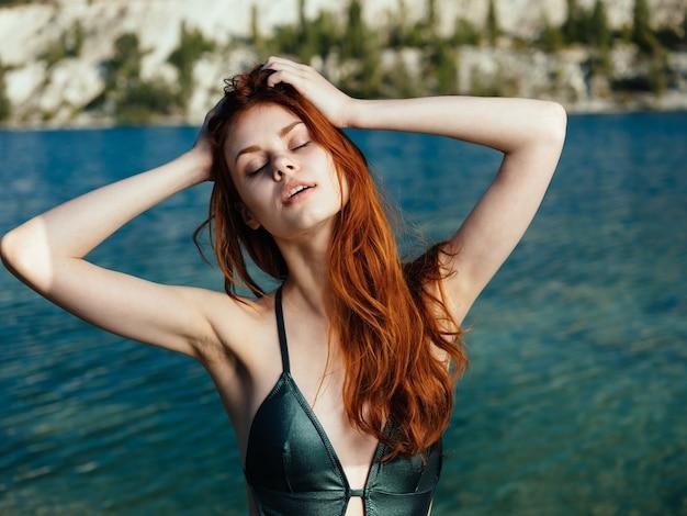 緑の水着サングラスの女性透明な水川海の自然