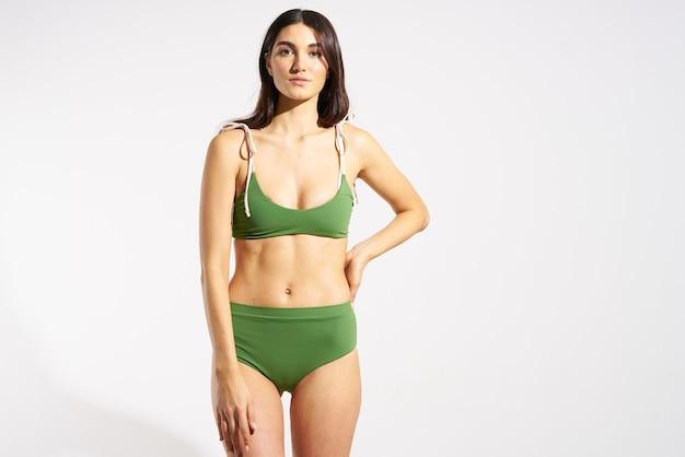 緑の水着ビーチファッション旅行ポーズの女性。高品質の写真