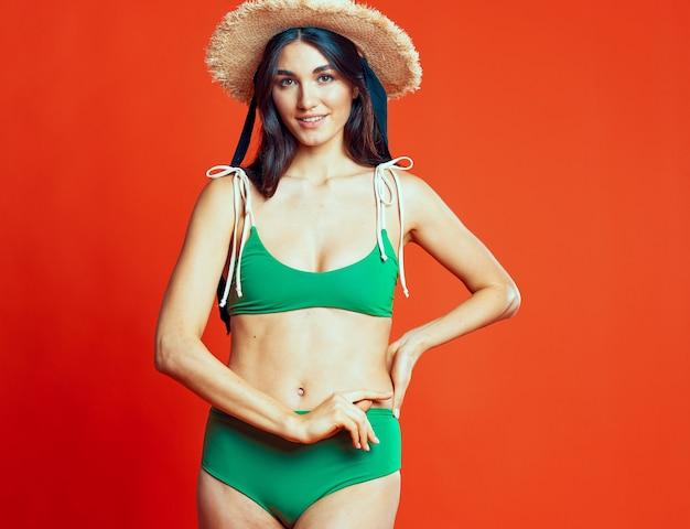 緑の水着のエキゾチックな夏のビーチシーズンの女性