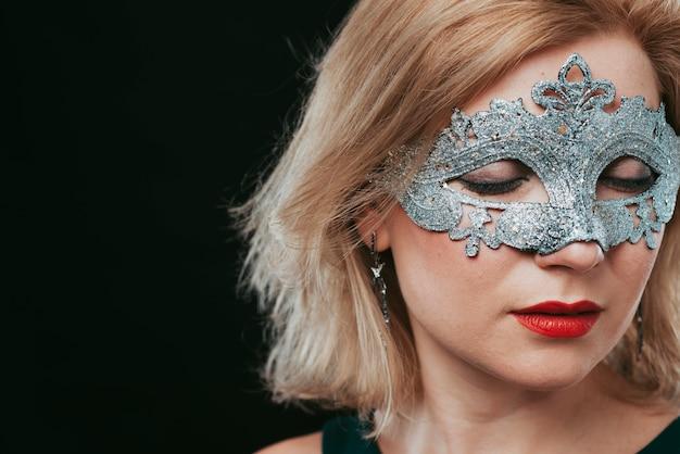 Женщина в серой карнавальной маске закрывает глаза