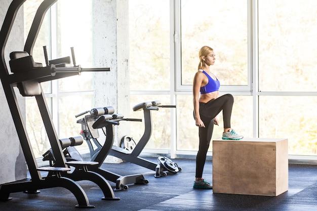 Женщина в тренажерном зале делает упражнение по кроссу на коробке