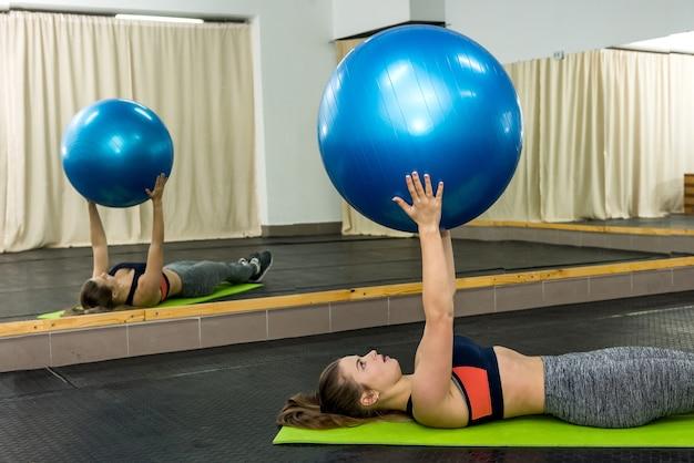 큰 공 연습을하는 체육관에서 여자