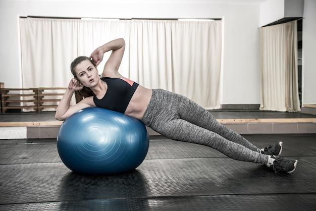 大きなボールでエクササイズをしているジムの女性
