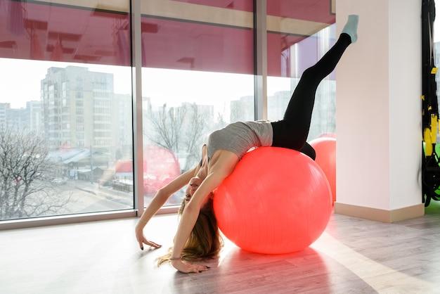 体操ボールで働くジムの女性