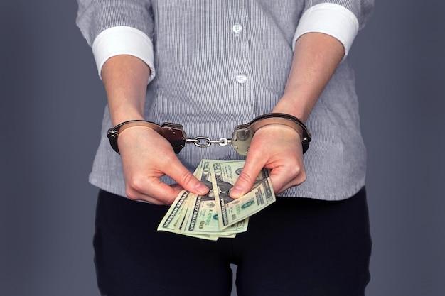 Женщина в наручниках, коррупция, взятка. женщина, держащая долларовые купюры в наручниках