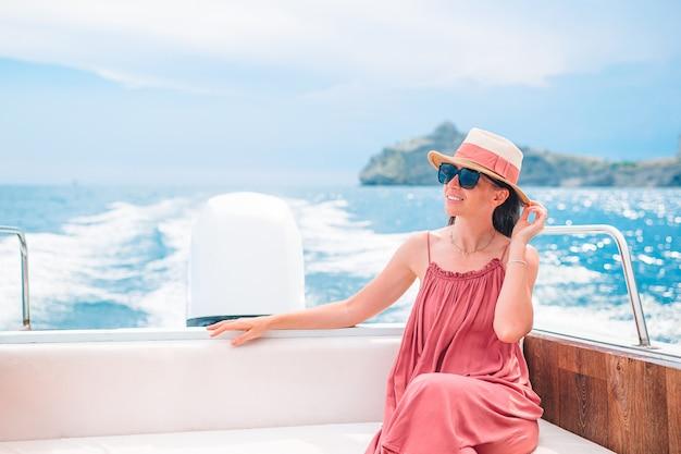 Женщина в шляпе и платье плывет на лодке в чистом открытом море