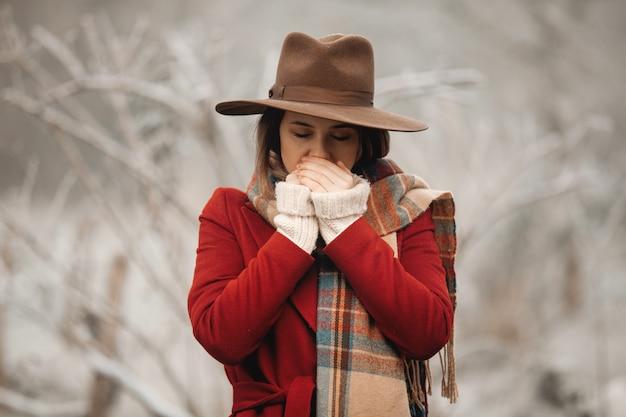 Женщина в шляпе и красном пальто в зимней сельской местности