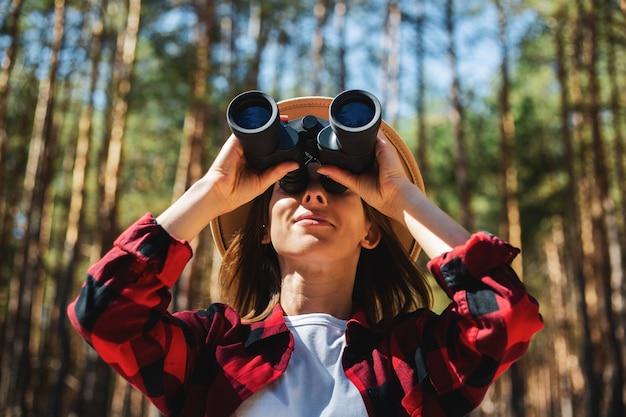 숲에서 쌍안경을 통해 찾고 모자와 붉은 격자 무늬 셔츠에 여자.