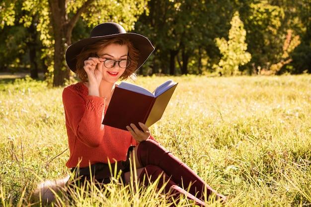 화창한 가을 날 공원에서 모자와 빨간 스웨터와 안경을 쓴 여자