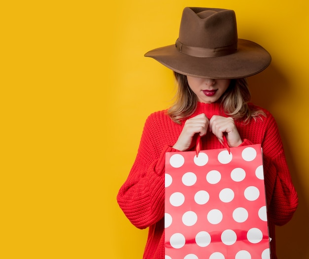 모자와 노란색 벽에 쇼핑백에 여자