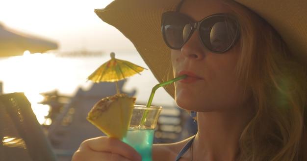 カクテルを飲む帽子とサングラスの女性
