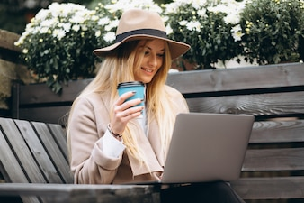 Woman in hat drinking coffee and working on laptop outside
