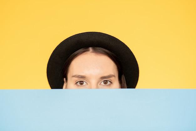 Женщина в шляпе смотрит через стену