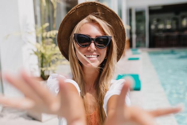 멋진 미소로 리조트에서 selfie를 만드는 모자에있는 여자. 아름 다운 유럽 여성 관광 수영장 근처 재미입니다.