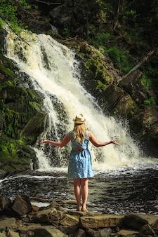 Женщина в шляпе медитирует возле лесного водопада.