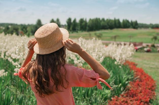 꽃 침대 근처 모자에 있는 여자. 분홍색 드레스를 입은 소녀, 밀짚 모자를 쓴 소녀는 꽃밭에서 태양을 마주하고 서 있다