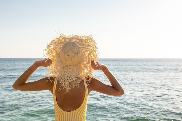 海の上の帽子の女性