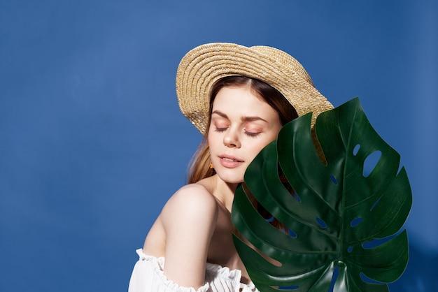 Женщина в шляпе пальмовых листьев путешествует летом экзотический синий фон. фото высокого качества