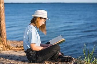 Woman in hat reading near sea