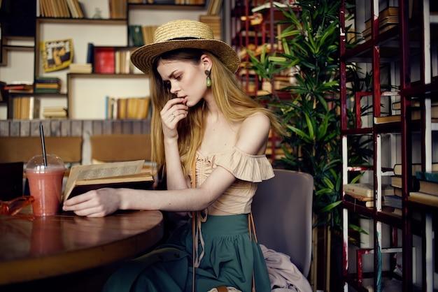 帽子をかぶった女性は、休暇を読んでカフェアカウントの飲み物の本に座っています。高品質の写真