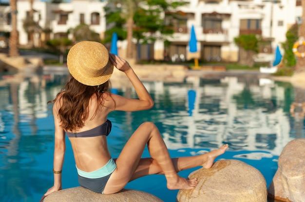 모자를 쓴 여자는 여름 수영장 스파 근처의 돌 위에 앉아 있습니다. 이집트에서 아름다운 이국적인 호텔 휴식