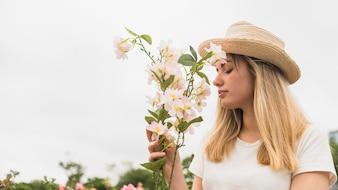 Woman in hat smelling light flowers