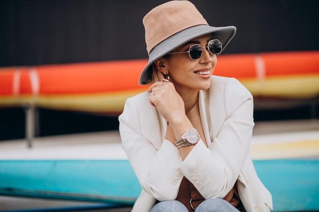 笑顔で電話を使用して帽子をかぶった女性