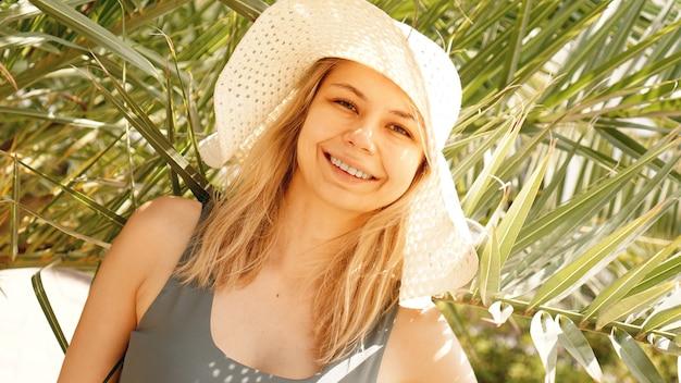 Женщина в шляпе под расслабляющими пальмами. тропический райский остров