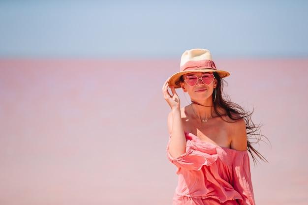 모자에있는 여자는 화창한 여름 날에 분홍색 소금 호수에 걸어