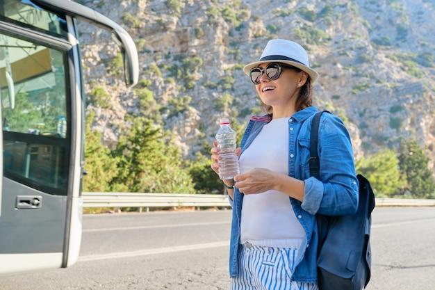 高速道路の山で水のボトル、ヒッチハイク、バスを停止、コピースペースで帽子をかぶった女性。自然、道路、観光、旅行、冒険、ロードトリップの概念の背景