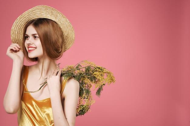 花の花束の装飾の豪華なピンクの背景を持つ帽子の女性