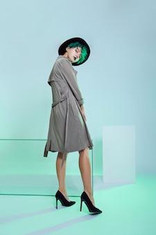 창조적 인 녹색 채색 머리와 메이크업, 머리카락의 독성 가닥 모자에있는 여자. 여자 머리, 전문 메이크업에 밝은 색 곱슬 머리. 망토에 문신을 한 여자