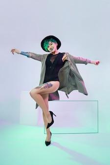 Женщина в шляпе с творческой зеленой окраской волос и макияжем, токсичными прядями волос. яркие вьющиеся волосы на голове девушки, профессиональный макияж. женщина с татуировкой в плаще