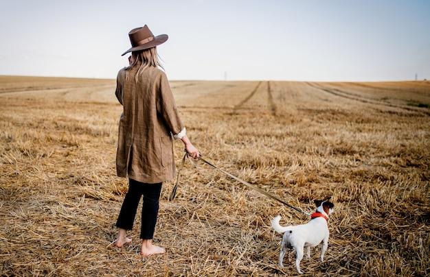 麦畑で犬と帽子をかぶった女性