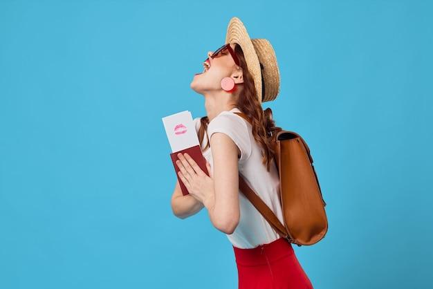 Женщина в шляпе с паспортом и билетами на самолет путешествия весело мечта синий фон