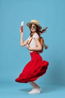 여권과 비행기 티켓이 있는 모자를 쓴 여성은 재미있는 꿈의 파란색 배경을 여행합니다.