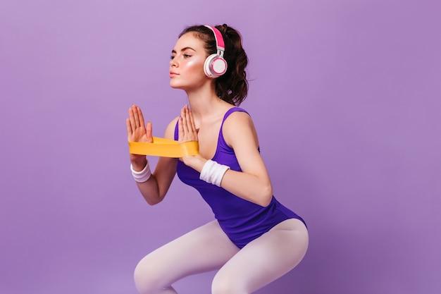 헤드폰을 착용 한 여성은 스포츠 용 탄성으로 스쿼트를하는 올바른 기술을 보여줍니다.