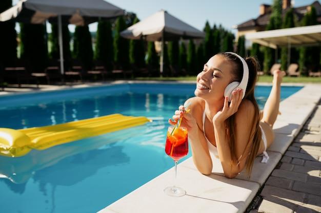 ヘッドフォンの女性はプールでカクテルを飲みます