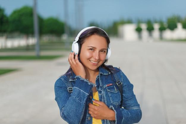 ヘッドフォンの女性。屋外で音楽を聴いているヘッドフォンで感情的な若い女性。
