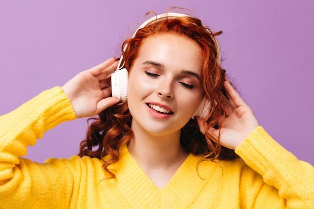 헤드폰에있는 여자는 라일락 벽에 그녀가 좋아하는 노래를 즐긴다
