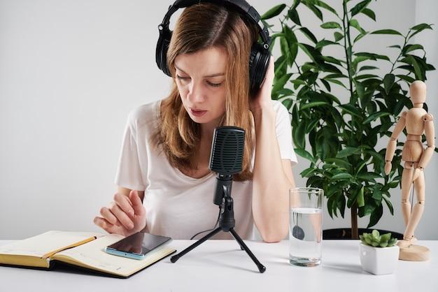 Женщина в наушниках имеет онлайн-уроки дома, электронное обучение и концепция подкастов