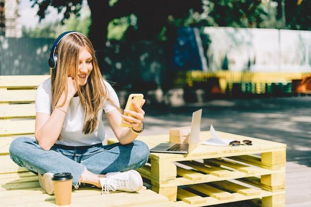 Женщина в наушниках с видеозвонком